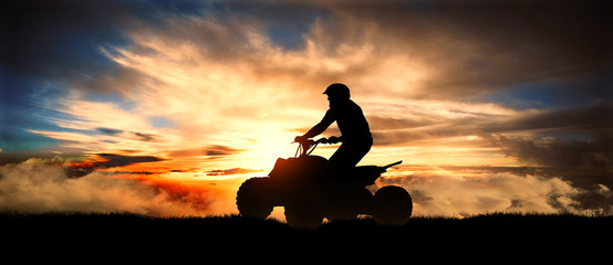 Young man rides an ATV over background of mountains at sunset