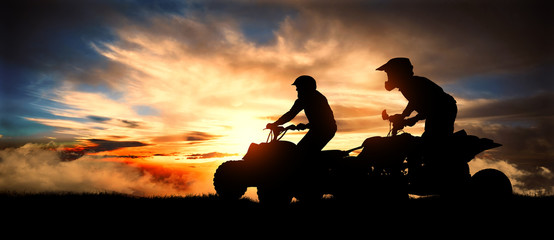 Two young men ride an ATV on the hill at sunset