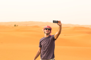 Young tourist man in the desert taking a photo.