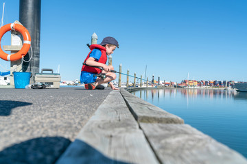 Boy sits on dock fishing