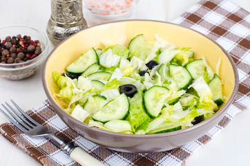 Healthy food. Vegetarian salad from iceberg, fresh cucumber and black olives