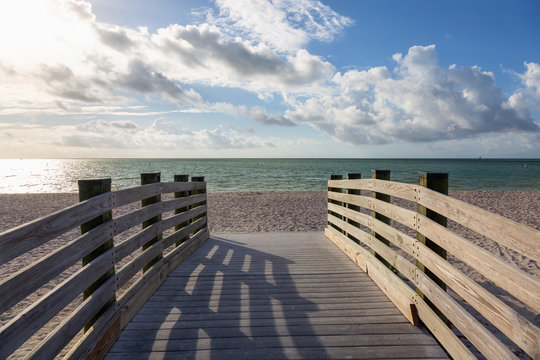 Wooden platform on a sandy beach during a vibrant sunny day. Taken in Sombrero Beach, Marathon, Florida, United States.