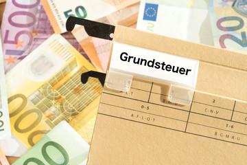 Euro Geldscheine und ein Ordner mit dem Aufdruck Grundsteuer