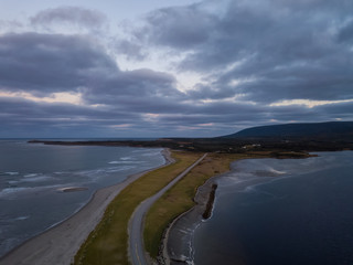 Aerial view of a beach on the Atlantic Ocean Coast during a dramatic sunrise. Taken in Codroy Valley, Newfoundland, Canada.