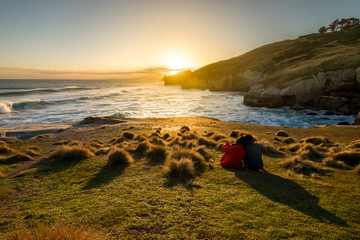 A girl leans over the shoulder of a man. The couple is enjoying beautiful sunset at Tunnel Beach of New Zealand. The sunset produces amazing orange glow. The coast is extremely stunning. Wall mural