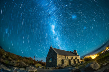 An abandoned house under the beautiful night sky. There are stars and milky way. This is a famous tourist destination in New Zealand. This image has star trail to show the earth rotation. Wall mural