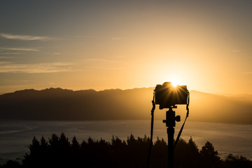 A travel image of a camera set up to shoot sunset on top of a hill in New Zealand. In the distance, one can see sunset and outline of a mountain. Below are the ocean and tree line.