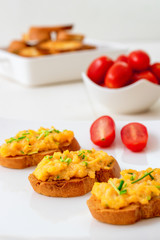 White plate with toasts and scrambled eggs, chive herbs and cherry tomatoes on white table background. Grilled bread with scrambled eggs and vegitable.