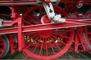 Close-up of the heavy iron wheels of a historic locomotive .