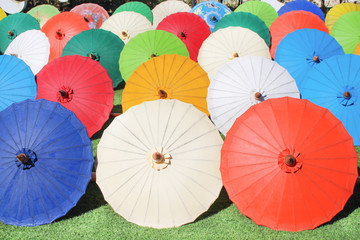 Colorful multicolored paper umbrella group on grass floor, decoration for background