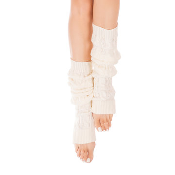 Female slim legs in white leg warmers. White pedicure, isolated on white background