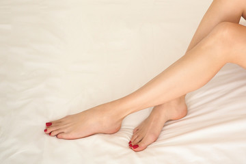 Female well groomed bare feet with classic red pedicure on white bedding, close up