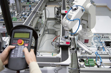 Man is holding teach panel (tablet) to control a robotic arm which is integrated on smart factory manufacturing line. industry 4.0 automation line which is equipped with sensors and robotic arm.