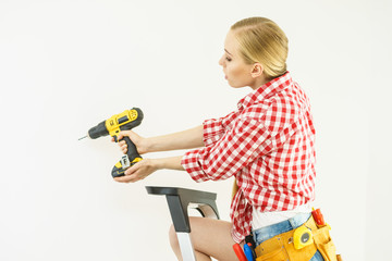 Woman drilling in wall