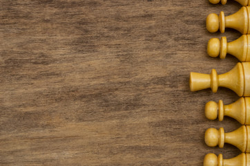white chess figures on the brown wooden table background