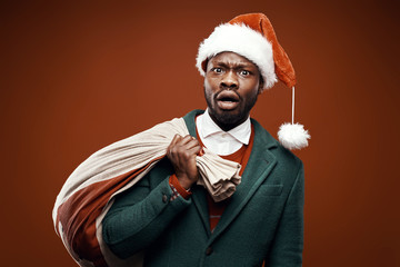 Modern Santa Claus. Surprised man posing in green coat and red sweater, with santa hat and bag. Studio shot, brown background