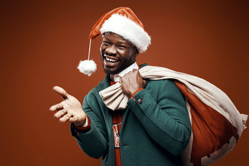 Modern Santa Claus. Smiling emotional man posing in green coat and red sweater, with santa hat and bag. Studio shot, brown background