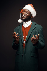 Modern Santa Claus. Smiling man in green coat and red sweater, with santa bag in hand. Studio shot, black background