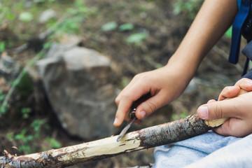Mano de un niño con navaja quitando corteza rama en bosque