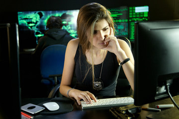 Cool strong female police woman studying hacker code