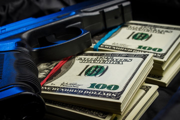 Bundle of dollars with a gun in a black bag