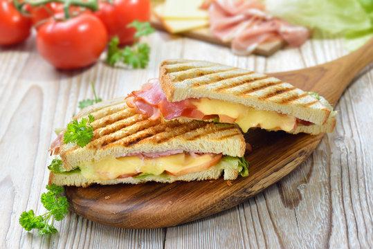 Getoastetes und im Kontaktgrill gepresstes italienisches Panini mit Schinken, Käse , Tomaten und Salat  - Pressed and toasted panini with ham, cheese, tomatoes and lettuce