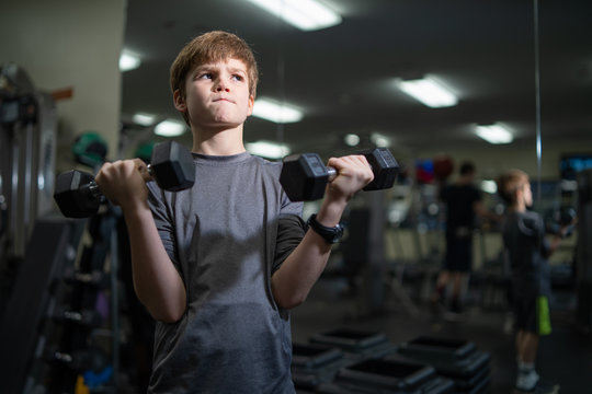 Little boy working out with weights in gym child fitness