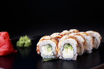 seafood restaurant, professional culinary, delicious japanese sushi. rolls with smoked eel served on black plate