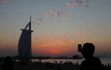 Man takes pictures after the last sunset of 2018 near Burj Al Arab hotel in Dubai