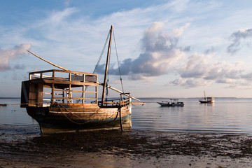 A big wooden sail boat on the water at the beach at sunrise in Mafia Island, Tanzania, with cloudy sky and calm water.