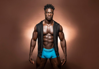 Muscular African American Black athletic fitness model wearing blue underwear and black hoodie with six pack abs in studio with dramatic lighting against a brown background