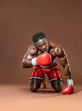 Muscular African American Black male sweaty boxer on knees,  knocked down trying to get up with dramatic lighting with a brown background
