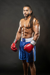 Muscular African American Black male  boxer with dreadlocks hair stands menecenly facing  towards the camera  with dramatic lighting with a black background
