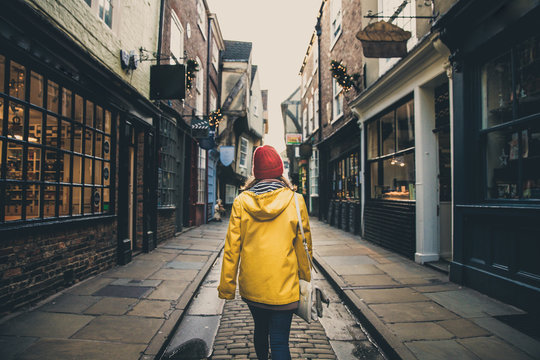 A rear view of a girl in a yellow coat walking along the historic street known as The Shambles in York, UK which is a popular tourist destination and medieval landmark in this ancient city