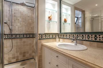 Modern bathroom with shower and washbasin for hygiene.
