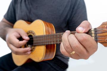 Young man playing ukulele with shirt and black pants.