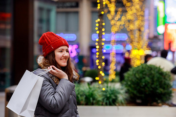 Young girl at the street with shopping bags colorful lights bokeh