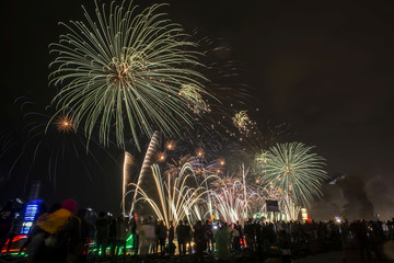 People watch as fireworks explode at Lagoon Beach Ancol during New Year's Eve celebrations in Jakarta