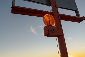 Backlit highway construction warning light at sunset