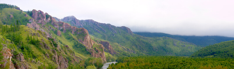 Panorama of the siberian summer landscape in the mountain ridge with fog. Valley of mountain river with green taiga forest view from high point. Beautiful scenery. Hiking in the mountains Khakassia