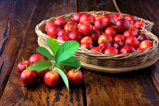 Acerola Cherry raw, fresh, in basket with heart shape on rustic wooden table, antioxidant fruits