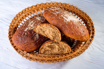 Pieces of black bread lie in a straw basket on a white wooden table. Bread close up