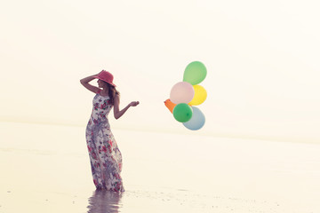 motivation or hope concept, follow your dream and inspiration, girl with balloons at sunset