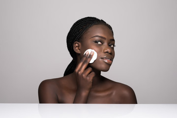 Young african girl applying foundation on her face using makeup sponge. Portrait of smiling african girl on white background