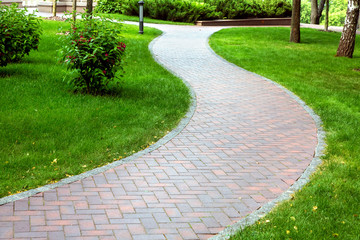 Pedestrian pavement paved with tiles, wavy pavement for walking in a park area with a green lawn. Wall mural