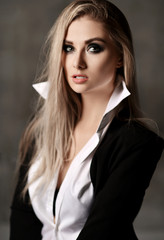 Young sexy sensual blonde fashion woman portrait posing in white man shirt and jacket on dark