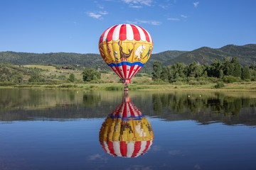 Poster Ballon Colorful hot air balloon with lake reflection