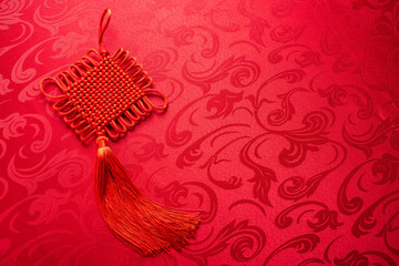 Chinese jigsaw knot on vintage jacquard red cloth background