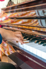 Vertical photo of young woman playing piano