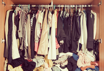 Pile of messy clothes in closet. Untidy cluttered woman wardrobe in vintage style.